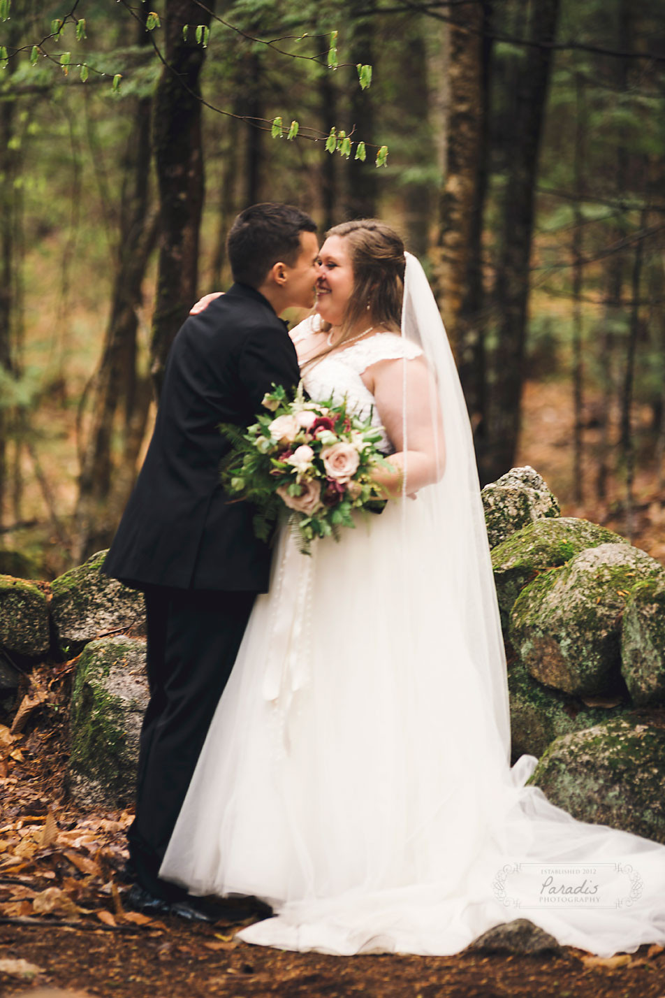 Sweet moment with bride and groom at their wedding in the maine woods