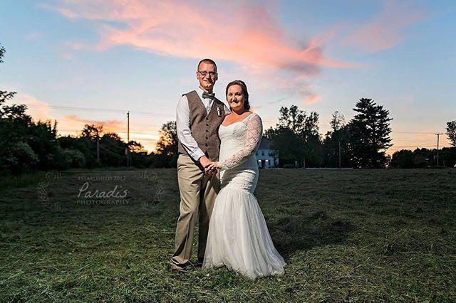 bride and groom with coolidge family farm wedding venue in background