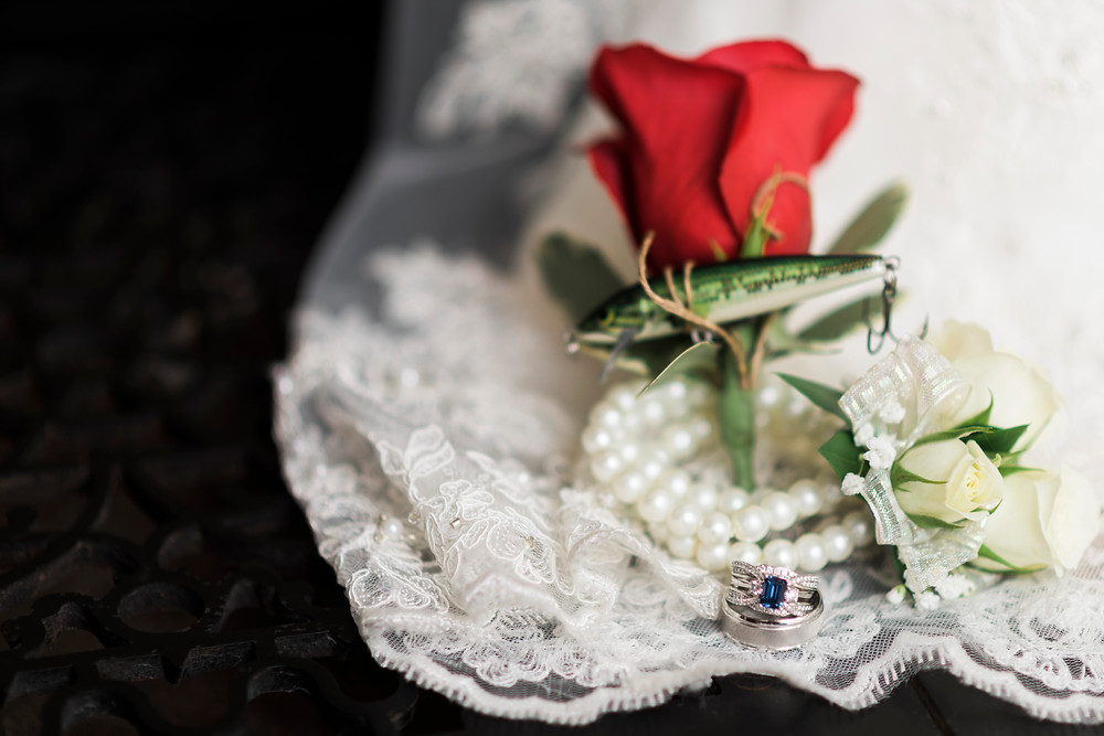 wedding details, fishing lure boutonniere, pearls, and wedding rings on lace wedding dress