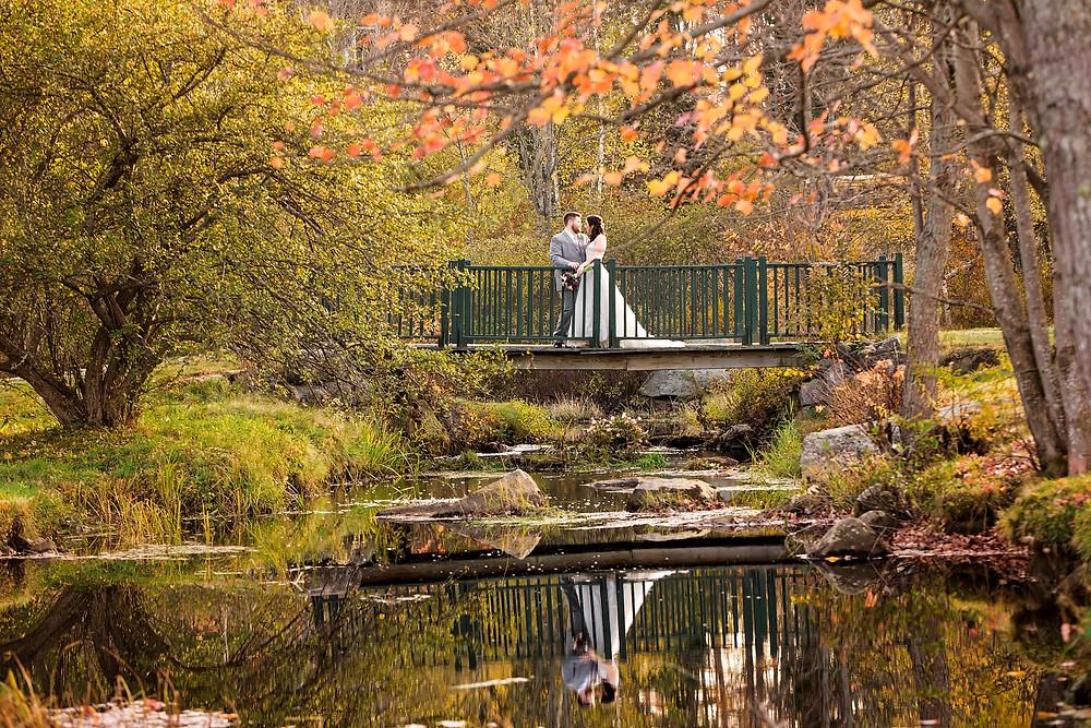 bride and groom on bridge at their bethel inn wedding in maine fall foliage peak