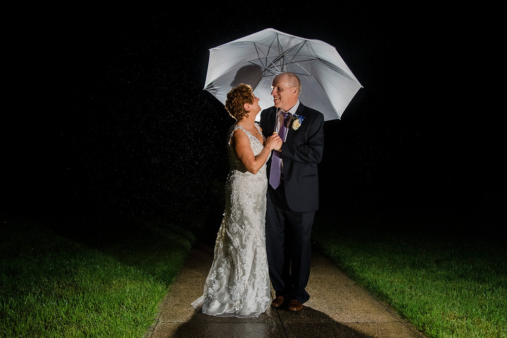 Bride and Groom standing under and umbrella in the rain at night on a path in the grass