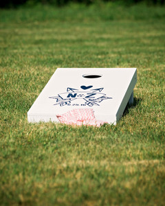Personalized cornhole board with bean bags in the grass