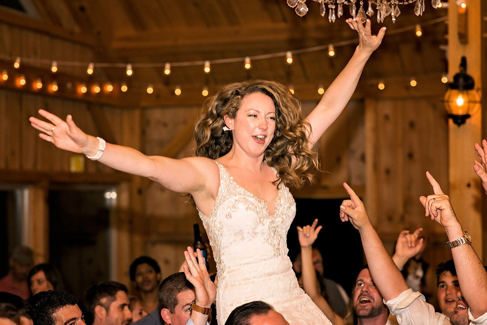 bride being tossed in the air at her wedding reception at Granite Ridge Estate in Maine