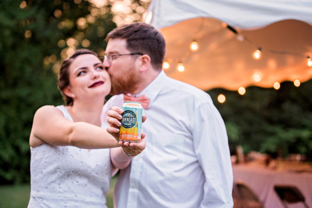 Groom kissing Bride holding their signature drink
