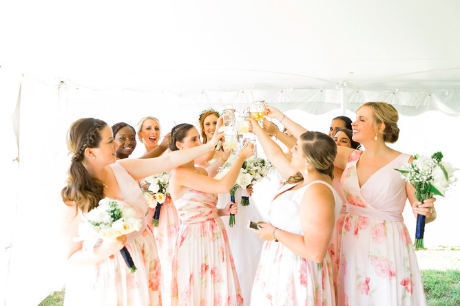 Bridesmaids and bride clinking their beer glasses under a tent on a sunny day