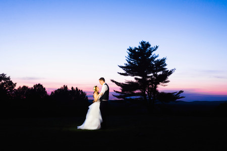Bride and Groom looking in eachothers eyes in a field with trees in the background after sunset