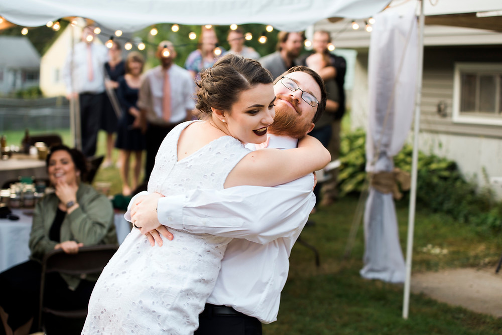 Groom lifting bride while dancing in their backyard wedding