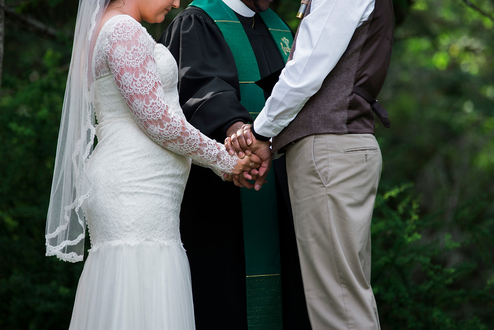 Bride and groom holding hands during ceremony with officiant's hand on theirs