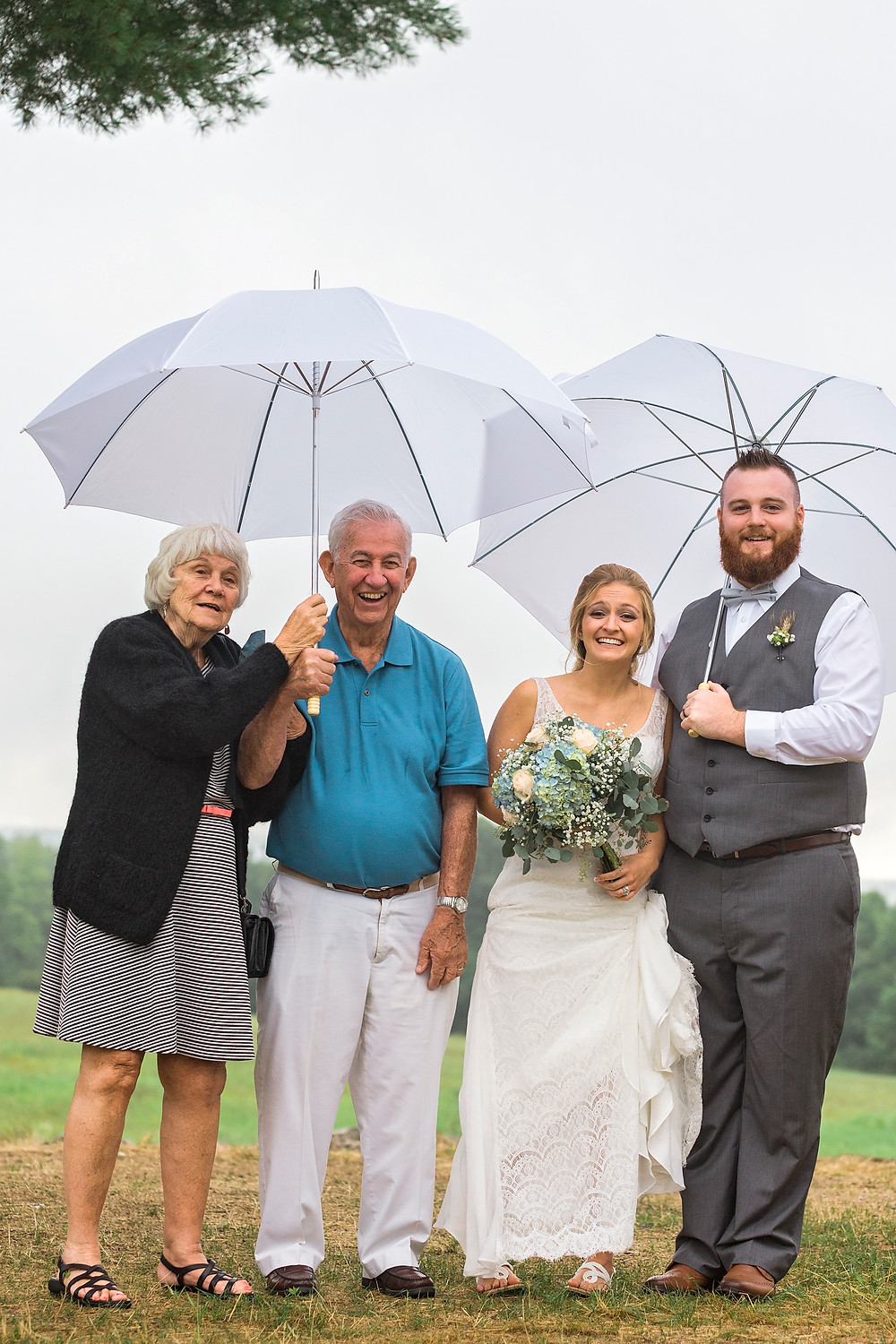 Bride and groom holding umbrella with grandparents on their wedding day