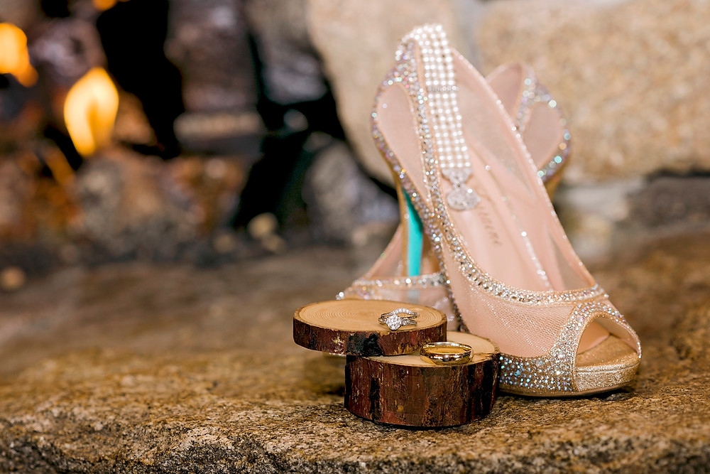 Bride's jewelry and shoes in front of the fireplace at Granite Ridge Estate