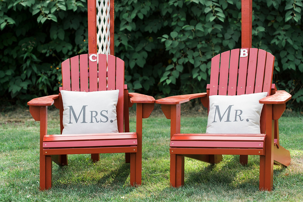 Mr & Mrs red Adirondack chairs with pillows