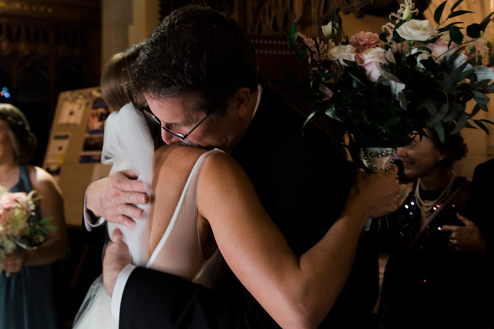 father of the bride embraces his daughter at her maine wedding