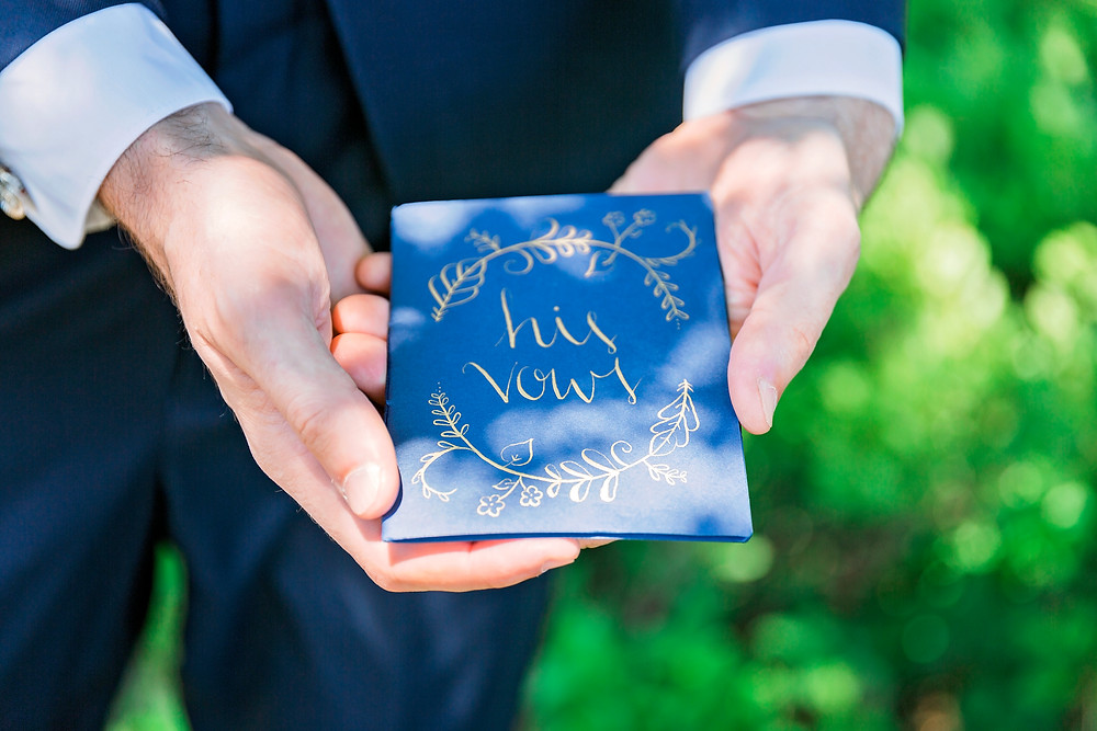 His vows blue notebook in groom's hands