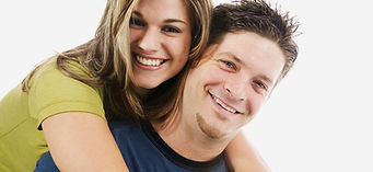 A woman riding piggyback on a man.  Both are smiling.