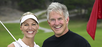 A smiling older man and woman going golfing