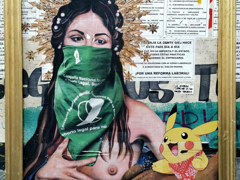 Noviembre 2019. Mural Santísima Dignidad con Pikachu enmarcado en dorado. palomarodriguez.cl es Pintora, orfebre y restauradora quien hizo este mural en las paredes del Centro Cultural Gabriela Mistral en Santiago. Mostrando dos iconos de la protesta social en Chile, una mujer semidesnuda encapuchada con el pañuelo verde en favor al aborto libre y la imagen de Pikachu quien se ha vuelto un personaje en las calles de Santiago durante las protestas desde el 18 de octubre de 2019. La tía Pikachu es Giovanna Grandón una mujer chilena que ha salido desde el inicio de las manifestaciones en Chile a apoyar el movimiento social en las calles. Este mural fue enmarcado por el colectivo @museodeladignidad quienes enmarcan murales relacionados a la dignidad y los vuelven una muestra de arte al aire libre. Este mural fue borrado el 19 de febrero de 2020 de forma arbitraria y sin permiso del centro cultural. Esta fotografía queda como documento de la expresión social y el arte relacionado a las protestas sociales en Chile.