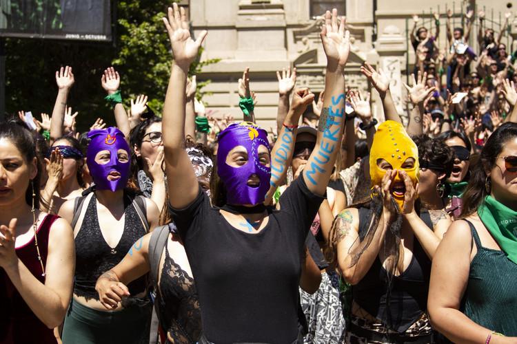 """29 november 2019. Vrouwen met maskers op nemen deel aan de performance van Een verkrachter op jouw weg van het collectief LASTESIS voor het Museum van Hedendaagse Kunst van Chili, het MAC, in Santiago. Een vrouw met masker symboliseert resistencia, verzet, rebellie. Met het masker beschermt de drager haar identiteit en lichaam voor de gevaren die sociaal protest met zich meebrengt. De klassieke protestmaskers ontwikkelden zich tot versierde maskers als reactie op de repressie van de overheid. De regering probeerde de dragers van maskers te criminaliseren, waarop vrouwen als vreedzaam protest en om de houding van de autoriteiten in vraag te stellen hun maskers omvormden tot kunstobjecten. In het nummer La Capucha (Het masker) van het colelctief La Chusma horen we zingen: """"La capucha no esconde solo responde."""" (""""Het masker verstopt niet, maar geeft repliek."""")"""