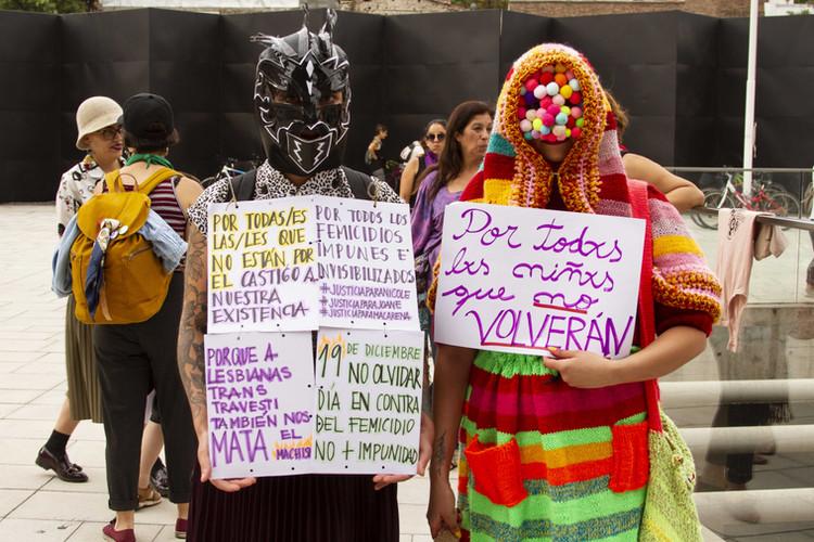 """19 december 2019. Nationale Dag tegen Feminicide. Herdenking in het Museum van de Herinnering en Mensenrechten in Santiago. Vrouwen met masker op verwijzen naar de slachtoffers van feminicide.  Links: """"Voor zij die er niet zijn, als straf van ons bestaan. Voor alle feminicides die onbestraft zijn gebleven. #GerechtigheidvoorNicole #GerechtigheidvoorJoane @GerechtigheidvoorMacarena Machismo doodt ook lesbische vrouwen, transgenders en travestieten. 9 december, niet vergeten, Dag tegen Feminicides. Basta straffeloosheid.""""  Rechts: """"Voor alle kinderen die niet thuiskwamen."""" Dit verwijst naar de kinderen die slachtoffer waren van misbruik en foltering in de staatsinstitutie Nationale Dienst van Minderjarigen van Chile (Spaanse acroniem SENAME) en naar het schandaal waarin deze institutie zich bevindt."""