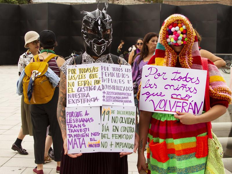 """19 de diciembre de 2019. Día nacional contra el femicidio conmemoración realizada en el Museo de la Memoria y los Derechos Humanos en Santiago. Mujeres encapuchadas, a la izquierda los carteles hacen referencia a las víctimas de feminicidios """"Por todas/es las/les que no están, por el castigo a nuestra existencia. Por todos los femicidios impunes de invisibilizados #JusticiaparaNicole #JusticiaparaJoane @JusticiaparaMacarena. Porque a lesbianas, trans, travesti también nos mata el machismo. 19 de diciembre no olvidar Día en contra del femicidio. No mas impunidad"""" a mano derecha """"Por todos los niños que no volverán"""" refiriéndose a los niños que han sido víctimas de abusos, torturas y asesinatos en el Servicio Nacional de Menores de Chile SENAME y al escándalo en que esta institución se ha visto envuelta en el ultimo tiempo."""