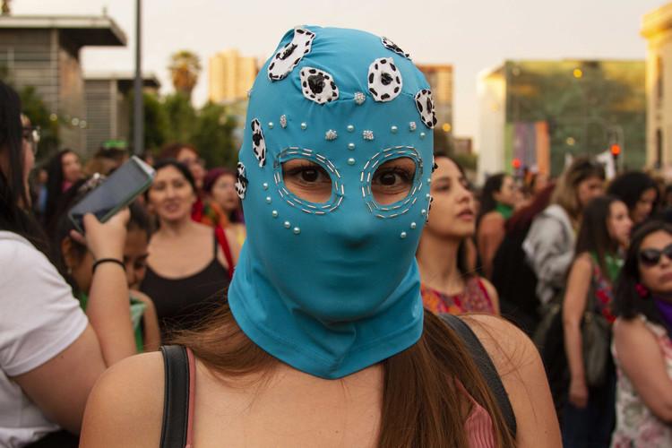 19 december 2019. Nationale Dag tegen Feminicide. Vrouw met masker tijdens de spontane mars na de herdenking in het Museum van de Herinnering en Mensenrechten. Deze vrouw verwijst naar de slachtoffers van staatsgeweld waarbij er volgens het Nationaal Instituut van Mensenrechten van Chili van het begin van de sociale onrust tot 20 maart  dit jaar 460 oogtrauma's zijn vastgesteld.