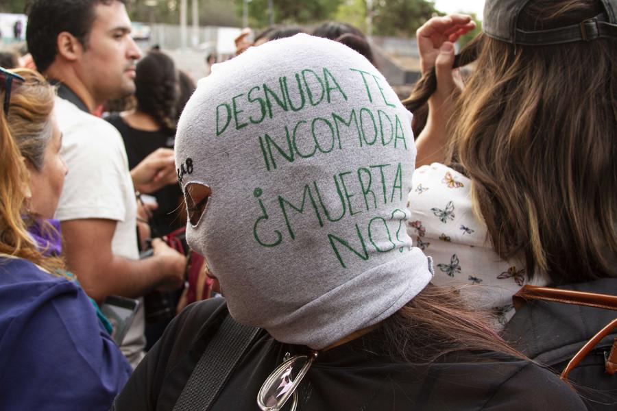 """Nationale Dag tegen Feminicide, een herdenking in het Museum van de Herinnering en Mensenrechten in Santiago. Vrouw met geborduurd masker: """"Wanneer ik naakt ben, voel je je ongemakkelijk. Wanneer ik dood ben niet?"""" De maskers zijn niet louter een decoratieve kunst, maar vooral een expressie van vrouwen tegen onrecht; in dit geval om het machogeweld aan te kaarten."""