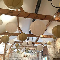 Gold and white paper lanterns at Upwaltham Barns