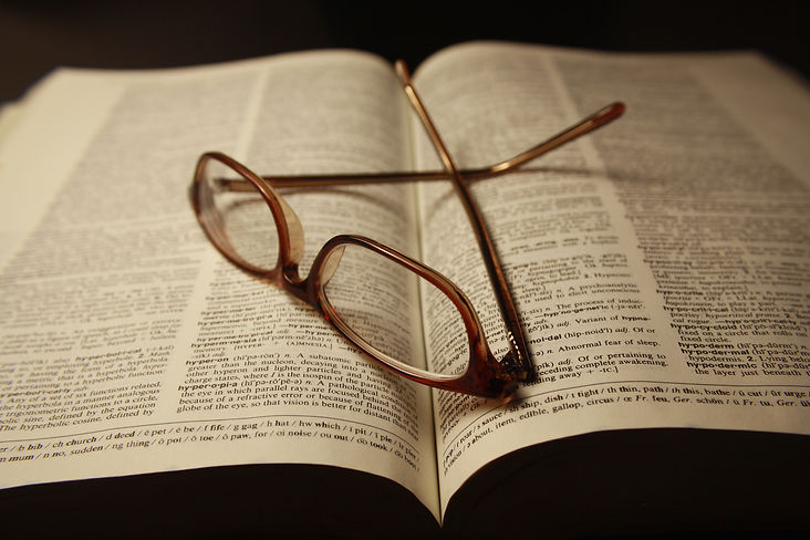 reading-glasses-atop-pages-of-open-dicti