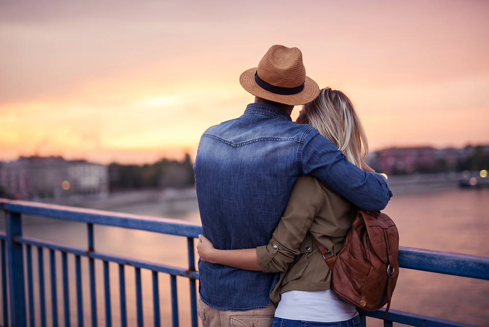 A color photo of a man and a woman embracing at sunset on a bridge.
