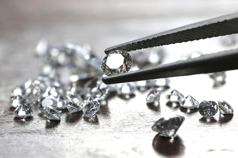 Image of several diamonds, one diamond being grasped by a pair of tweezers