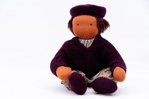 Zur Puppenkleidung gehören Strickjacke, Strickmütze, gestickten Schühchen, einer Stoffhose und eine Bluse