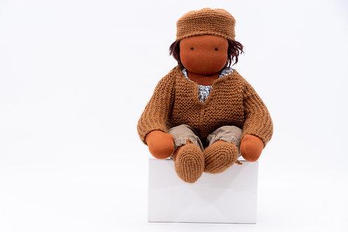 Zur Puppenkleidung gehört eine Strickjacke, Strickmütze, gestickten Schühchen, einer Stoffhose und eine Bluse