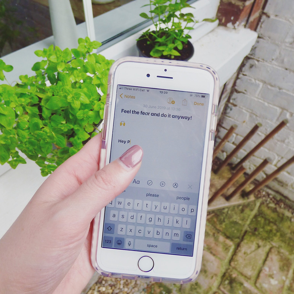 "Mobile phone reading ""feel the fear and do it anyway"" with plant pots in the background to demonstrate content marketing publishing doubts"
