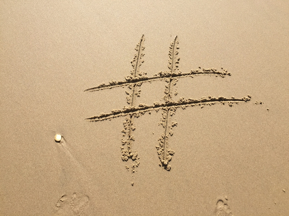 Hashtag in sand used on Zo Connected online marketing blog about Instagram captions