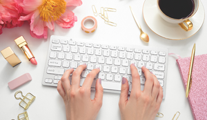 woman typing on keyboard surrounded by flowers, lipstick and coffee