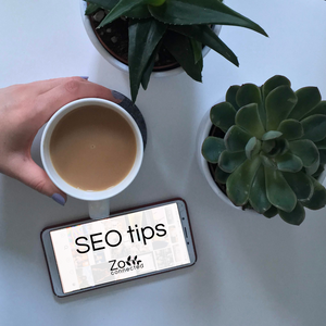 hand holding tea next to phone that reads SEO tips blog for small business owners