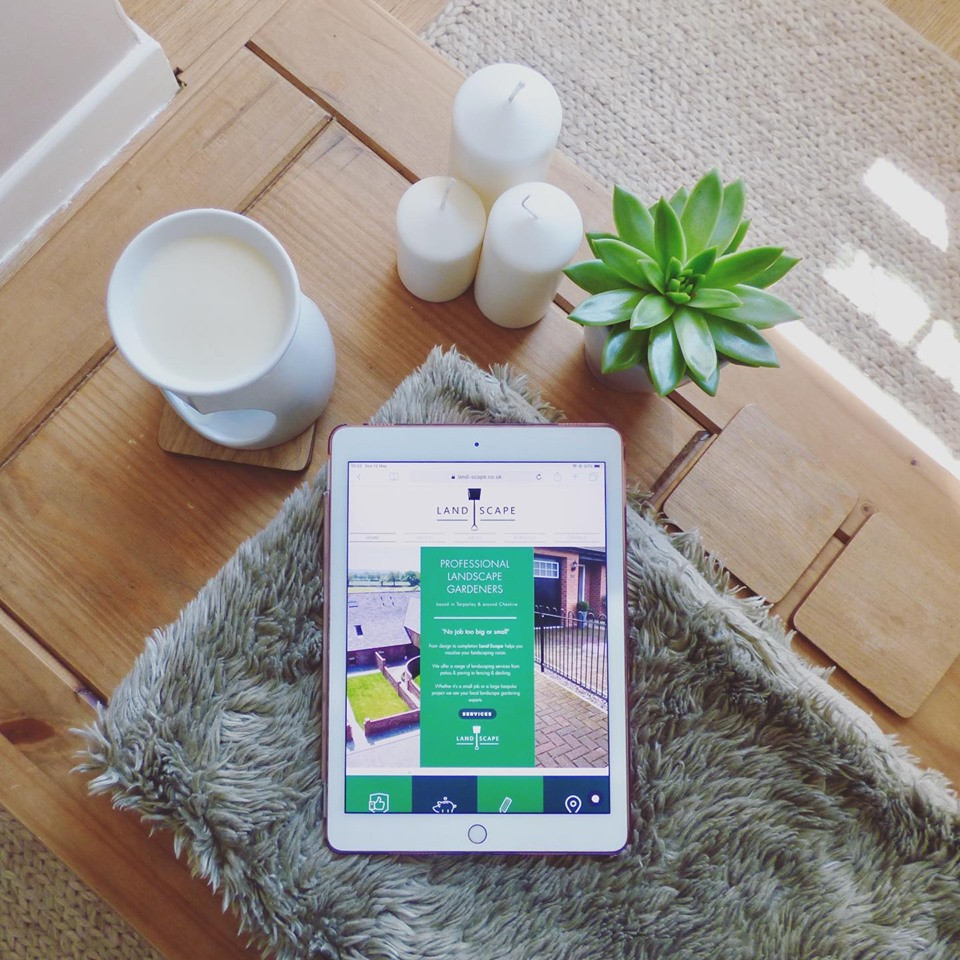 website design for landscape gardener on table next to candles and plant