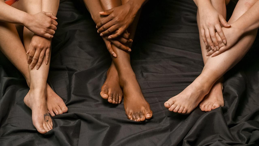 Three people's ankles crossed on floor