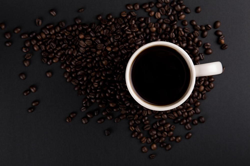 Cup of coffee near coffee beans