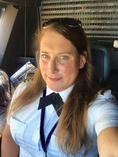 Female pilot taking a selfie in an airplane cockpit