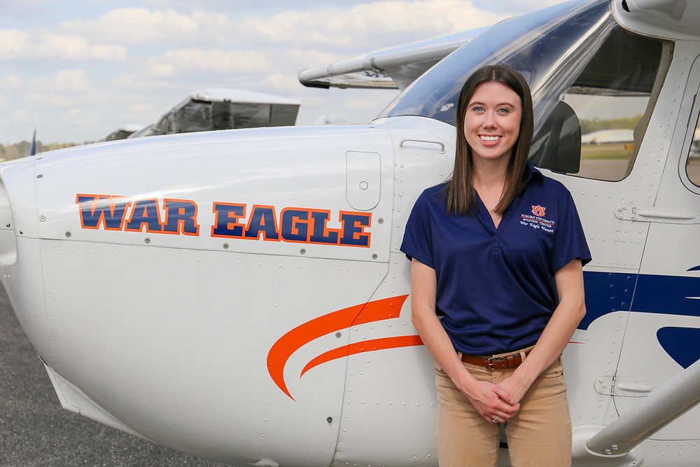 Mattie is standing next to a C-172 with Auburn University logo