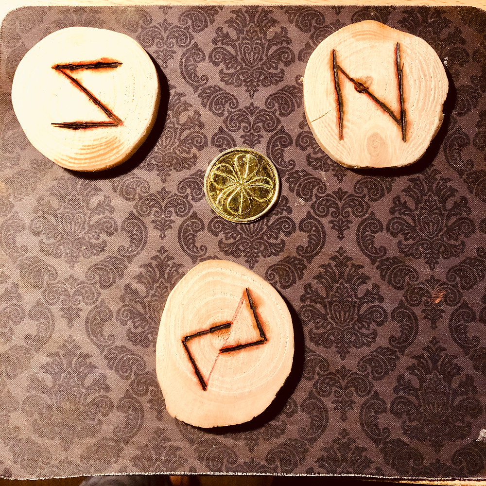 """Wooden coins emblazoned with Nordic runes and a """"golden"""" coin."""