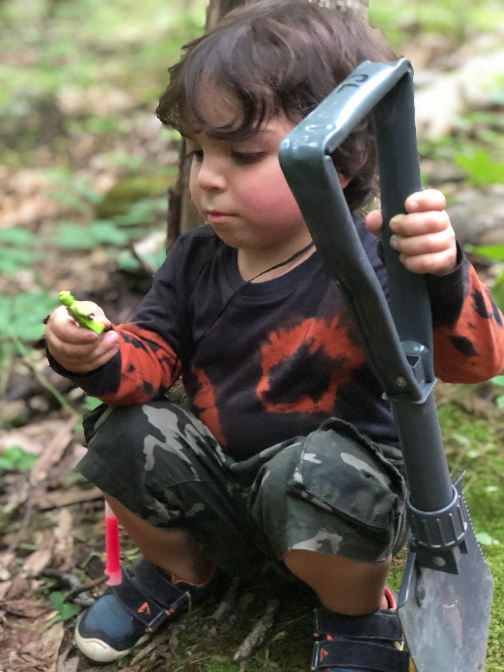 A child holds a toy figurine and a spade in either hand.