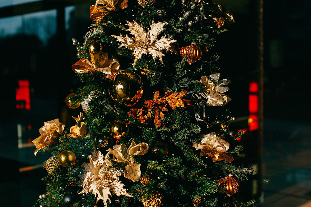 An elegant Christmas tree with gold bulbs and leaf ornaments.