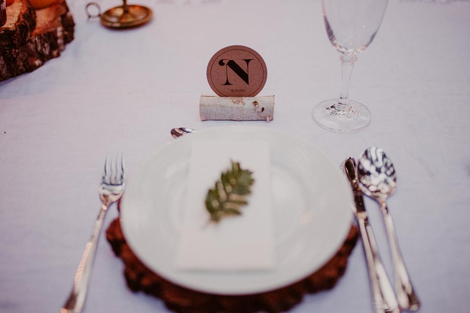 A place setting decorated with natural elements like sprigs of greenery.