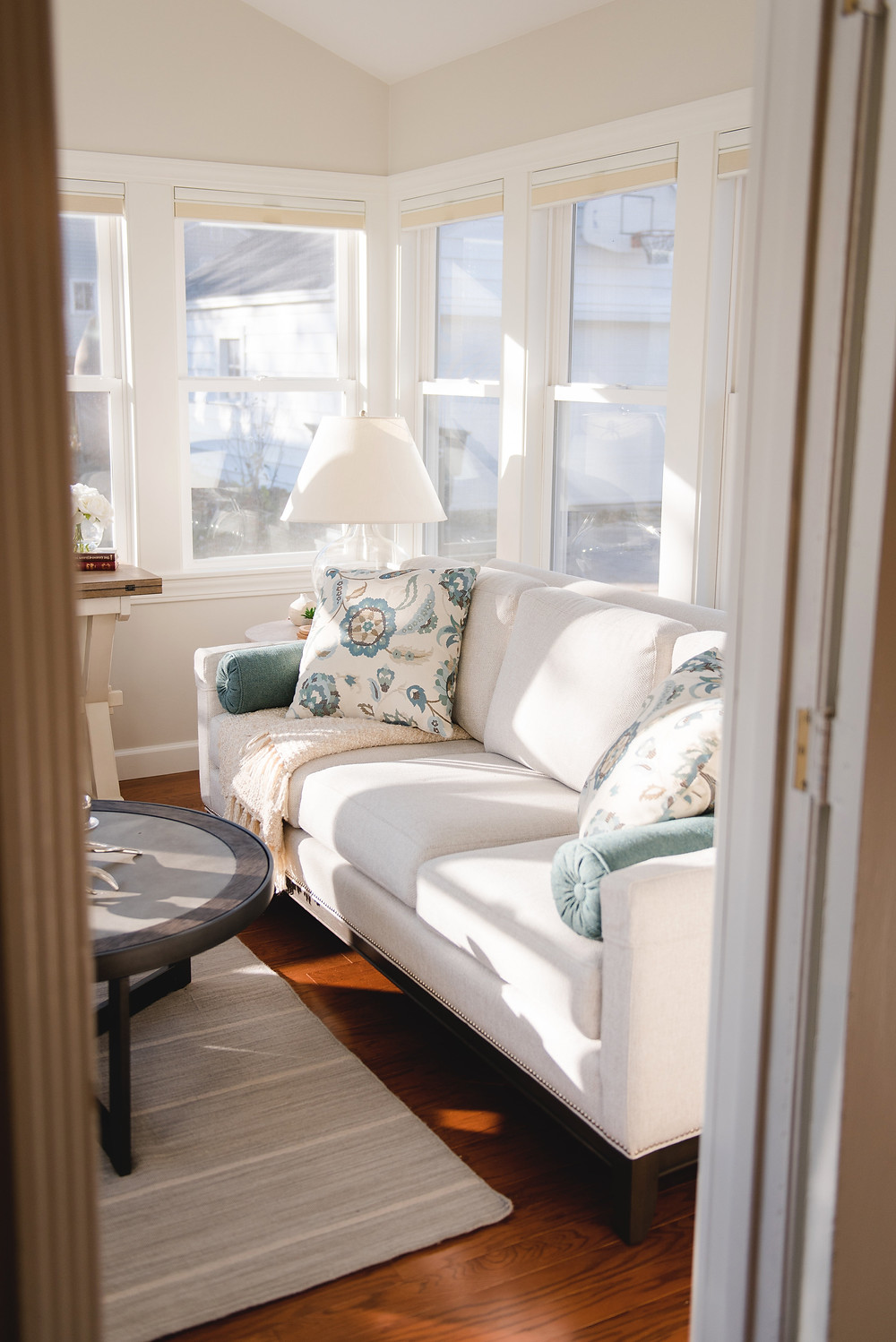 A white couch with teal accent pillows.
