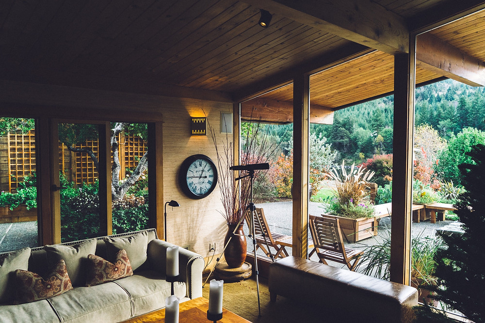 A rustic home with textured wood ceilings and windows looking out on a garden.
