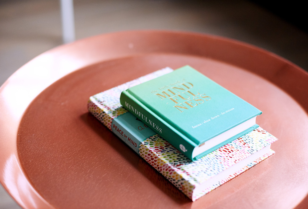A decorative plate with two books arranged on top of it.