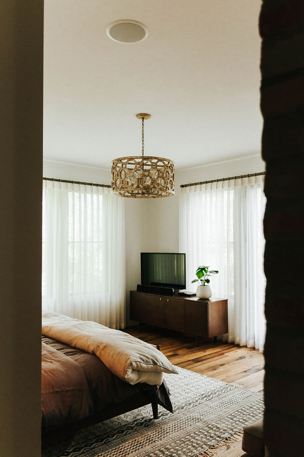 modern master bedroom with wood floors, gold light, and neutral tones