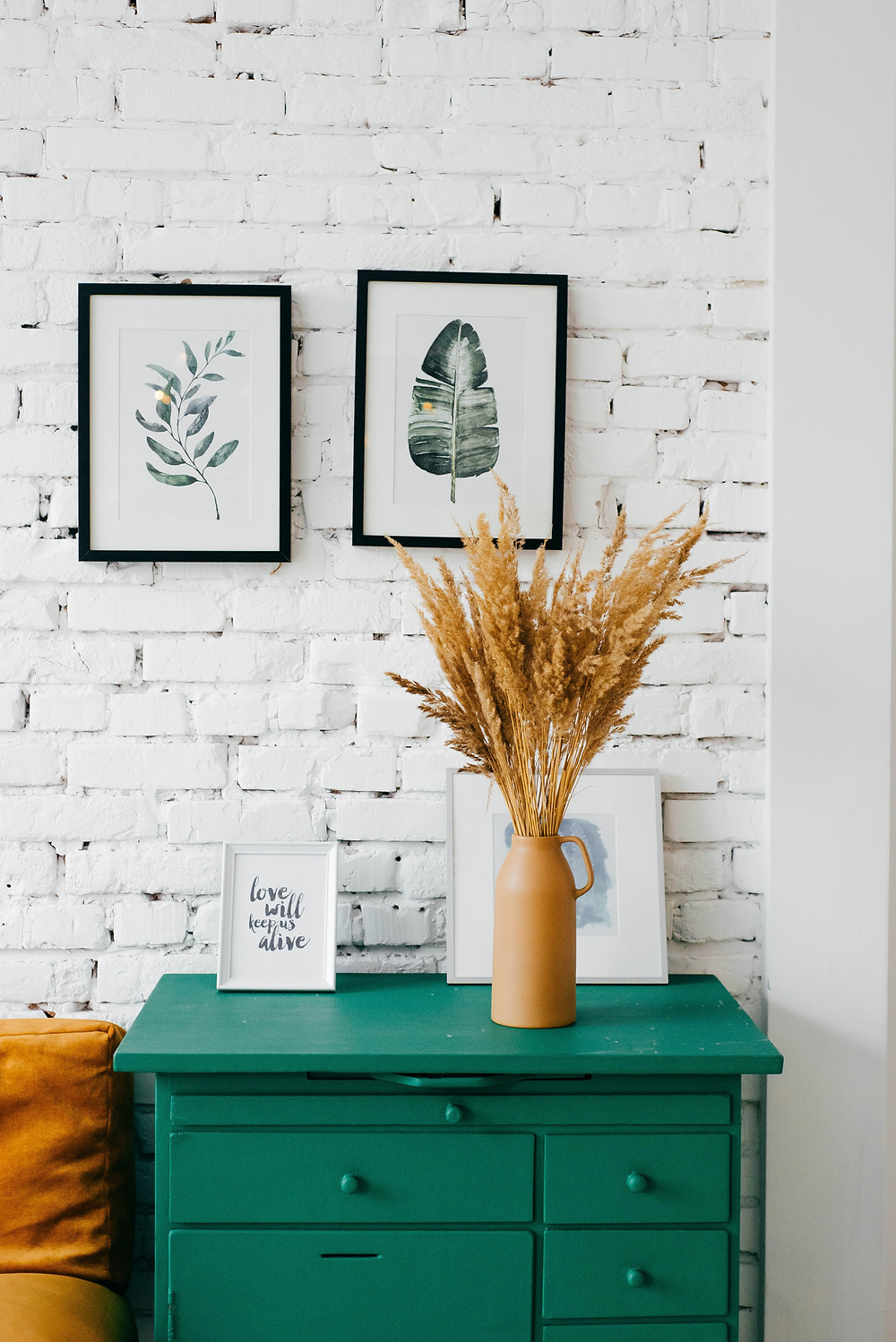 White brick and a green table pop in this photo of an entryway.