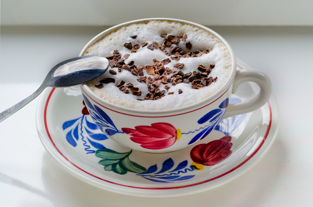 A flowered teacup full of a rich hot chocolate and topped with chocolate chips.